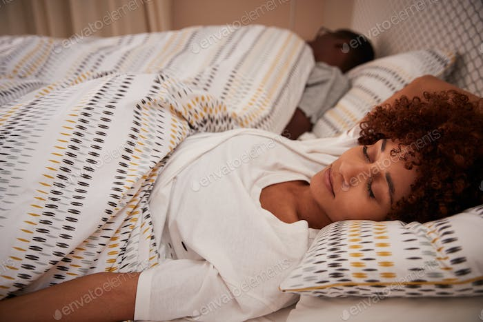 Millennial African American woman lying on her back asleep in bed, her partner in the background
