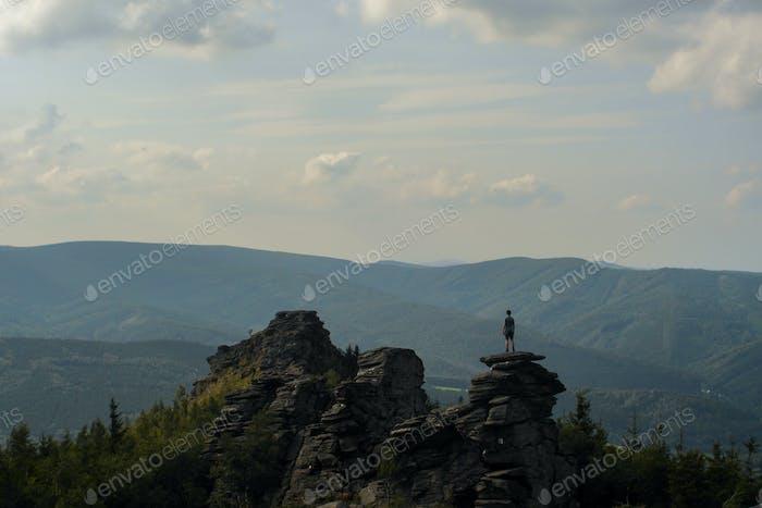 figure standing on a peak of the rock, overlookin landscape, czech republic