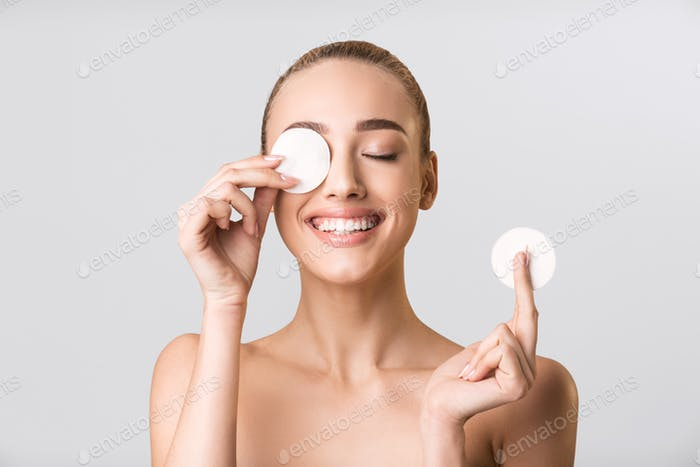 Young Woman Posing With Cotton Pads Covering Eye, Gray Background