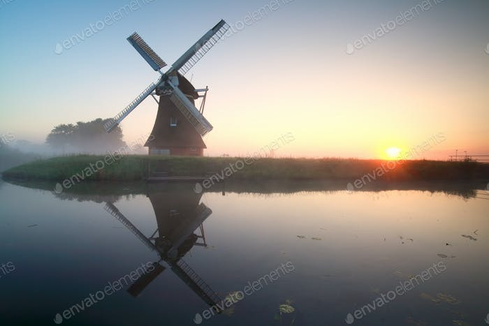 charming windmill by lake at sunrise