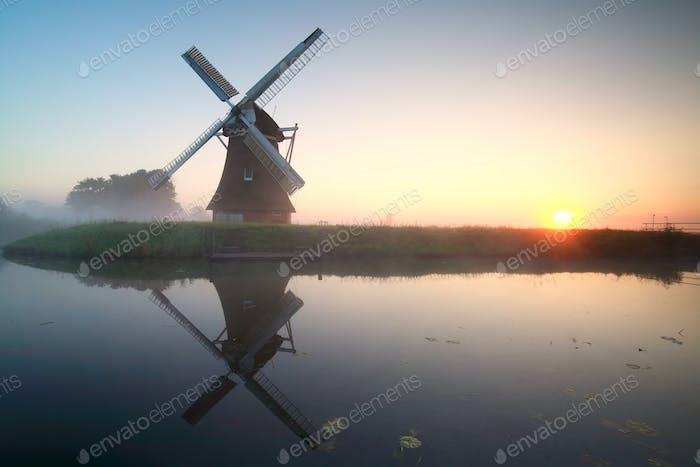 encantador molino de viento junto al lago al Amanecer
