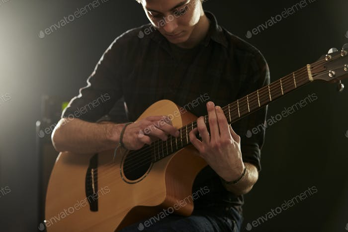 Man Using Tapping Technique On Acoustic Guitar