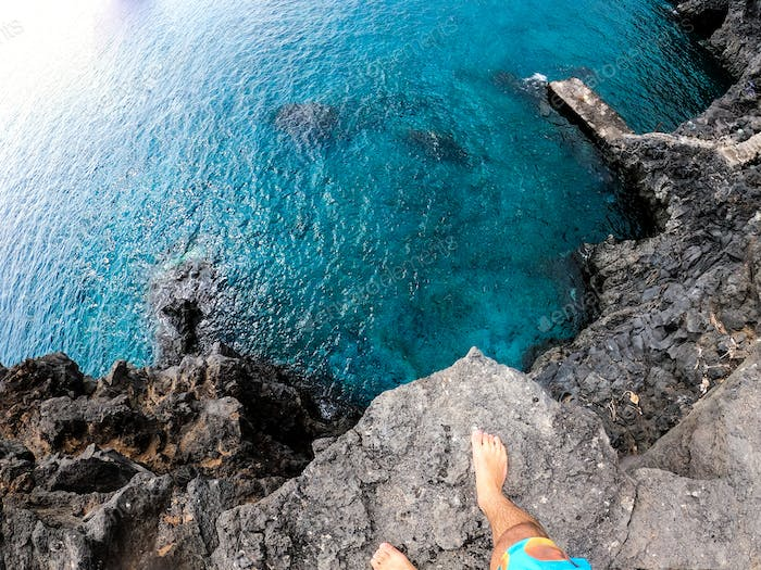 one man in pov or first person view jumping off a cliff to the water of the sea or ocean