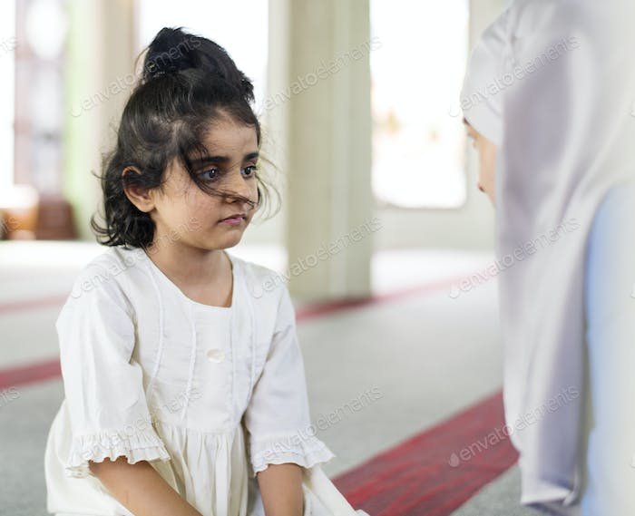 A little girl in the mosque with her mother during Ramadan