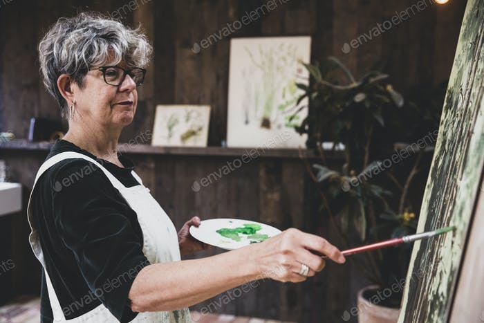 Senior woman wearing glasses, black top and white apron standing in studio, working on painting of