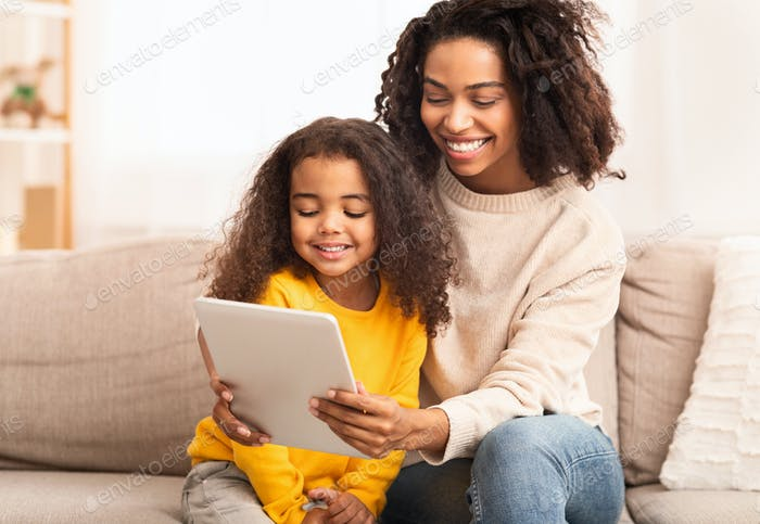 African American Mother And Daughter Using Tablet Sitting On Sofa