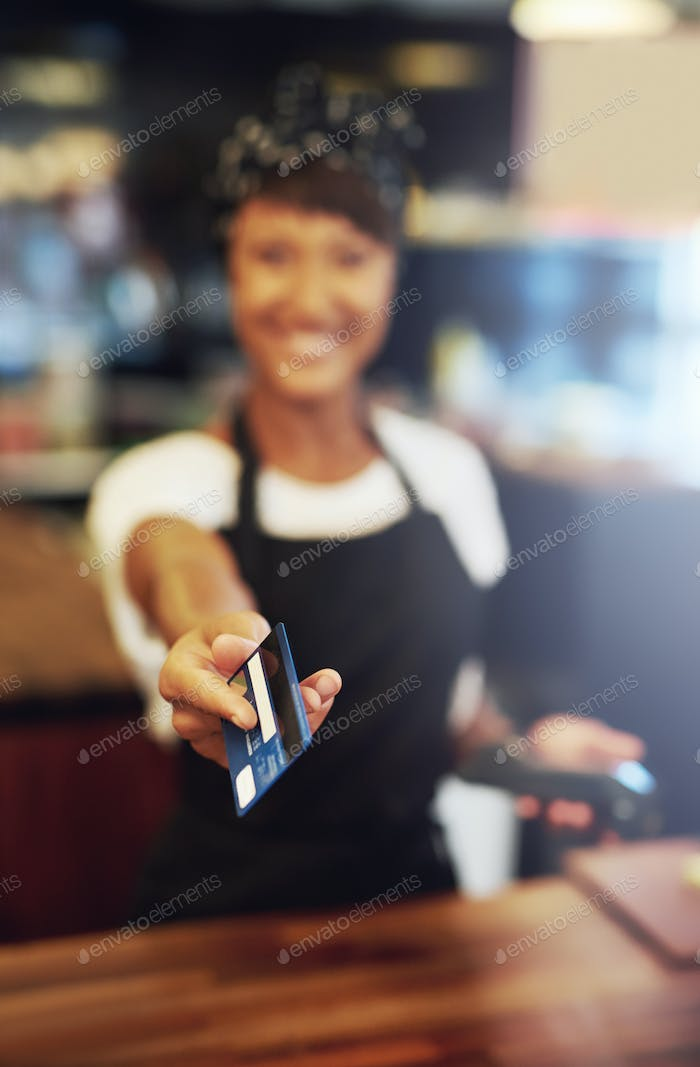 Young small business owner handing back a card