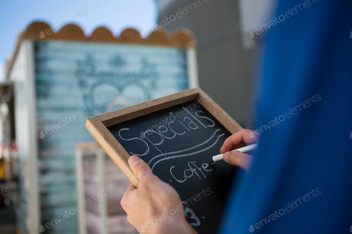 Cropped hand of owner writing menu