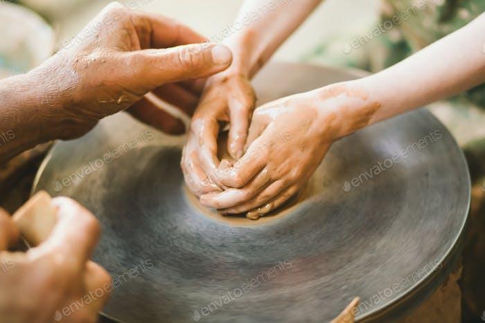 Potter teaches to sculpt a clay pot