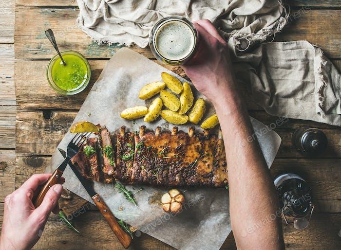 Man eating roasted pork ribs, holding fork and dark beer