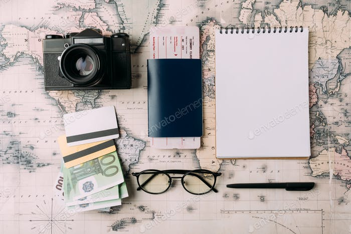 Flat lay of passport with ticket and money with credit cards on a map. tourism concept