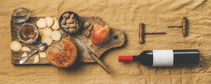 Wine bottle, vintage corkscrews and appetizers board, wide composition