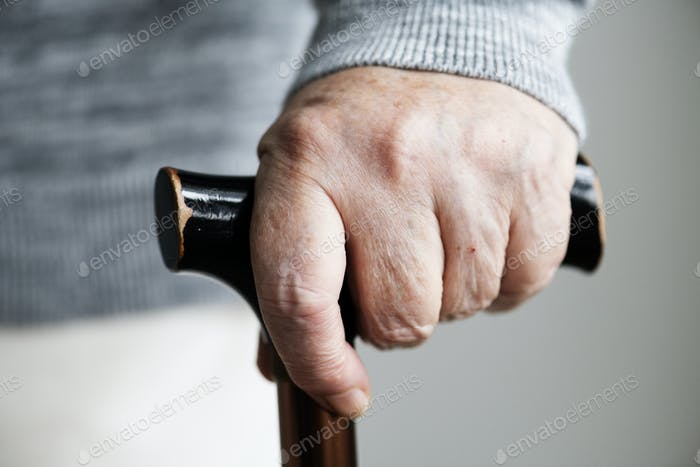 Closeup of elderly hand holding a walking stick