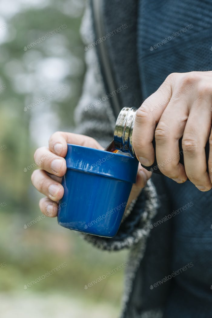 Mid section of man pouring coffee from insulated drink container
