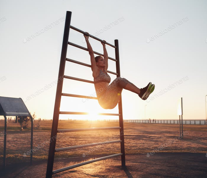 Young woman exercising on wall bars with her legs up