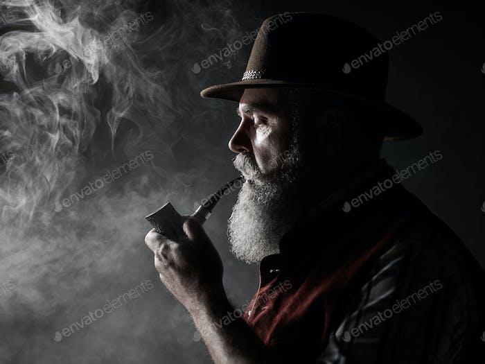 Черно-белый яркий портрет старшего курение табачной трубы