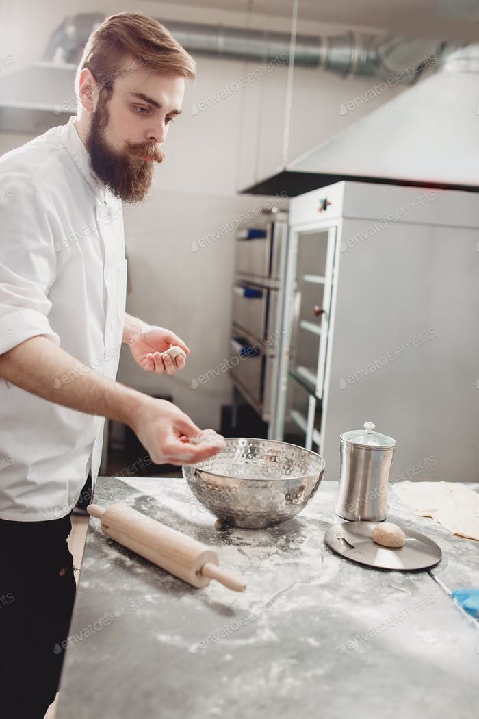 Professional baker divides dough into pieces on the table in the kitchen of the bakery