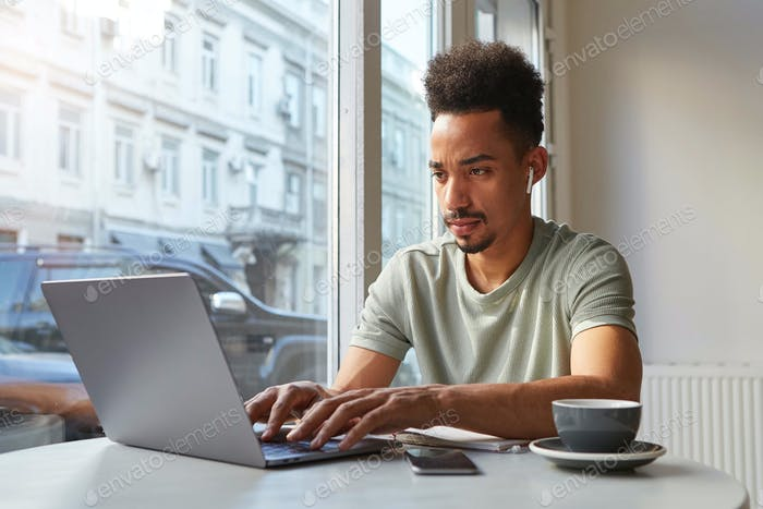 Portrait of concentrate young attractive African American boy, works at a laptop in a cafe