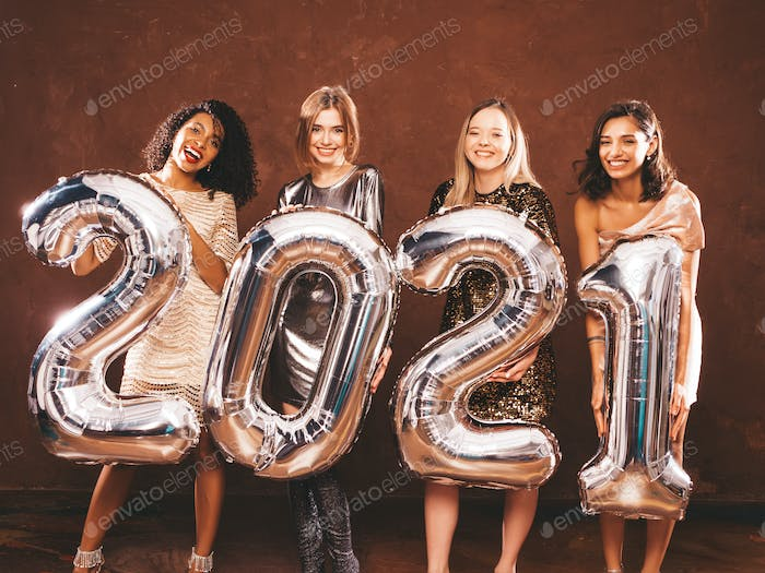 Portrait of four young stylish women holding silver 2021 balloons