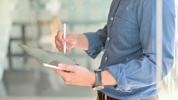 Два молодых бизнесмена консультировались по поводу своей работы, используя планшет, пока они стояли на рабочем месте.