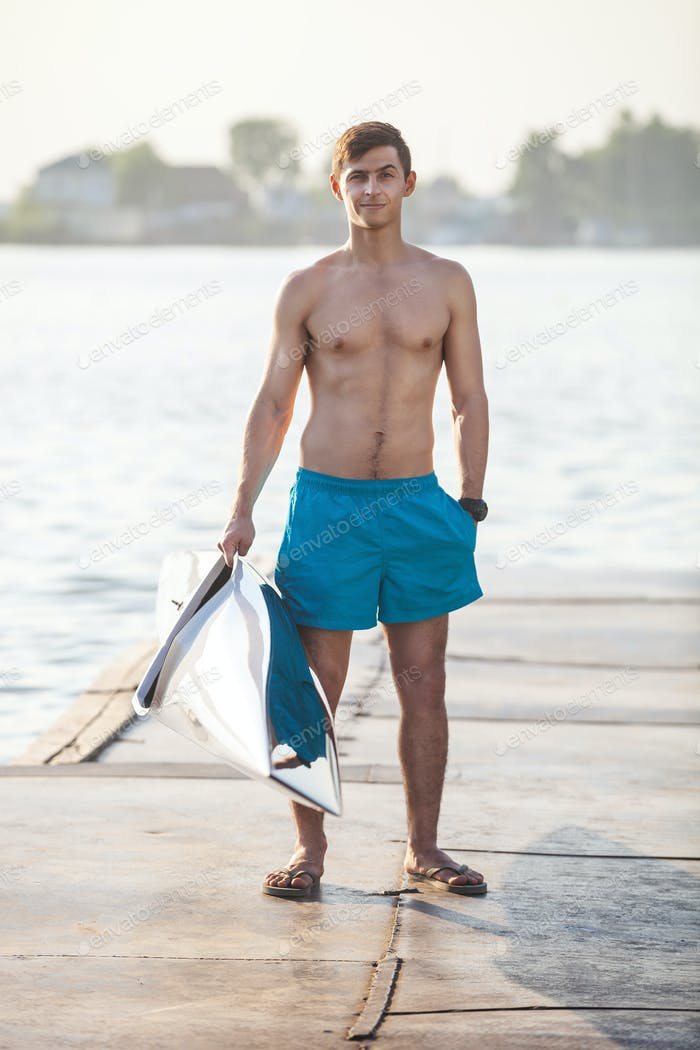 Young athletic man carrying canoe while standing on mooring