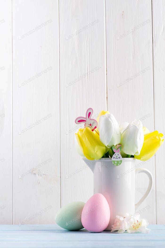 Congratulation Easter card with fresh tulips, handmade painted eggs and decotation against light