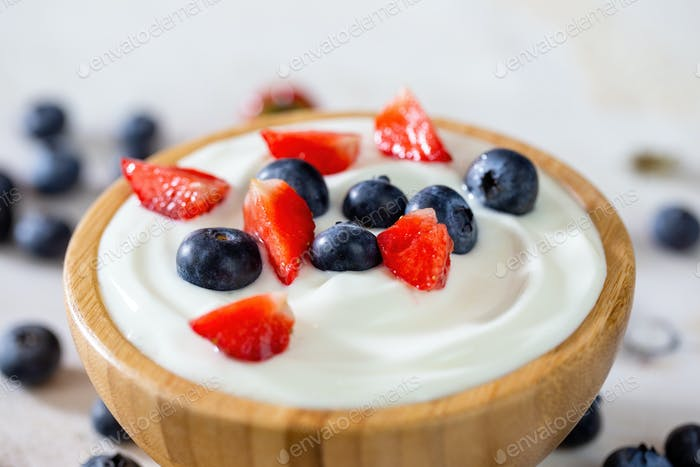 Wooden bowl filled with yoghurt, strawberries and blueberries in detail