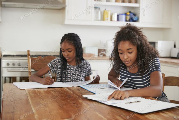 Two Sisters Sitting At Table In Kitchen Doing Homework