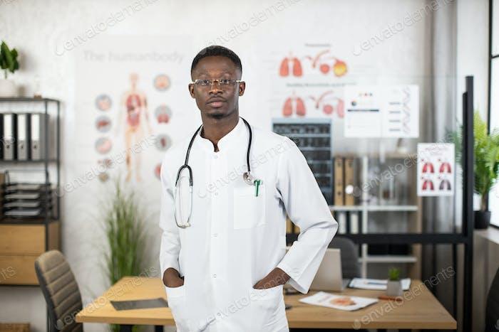 African american man doctor in lab coat posing indoors