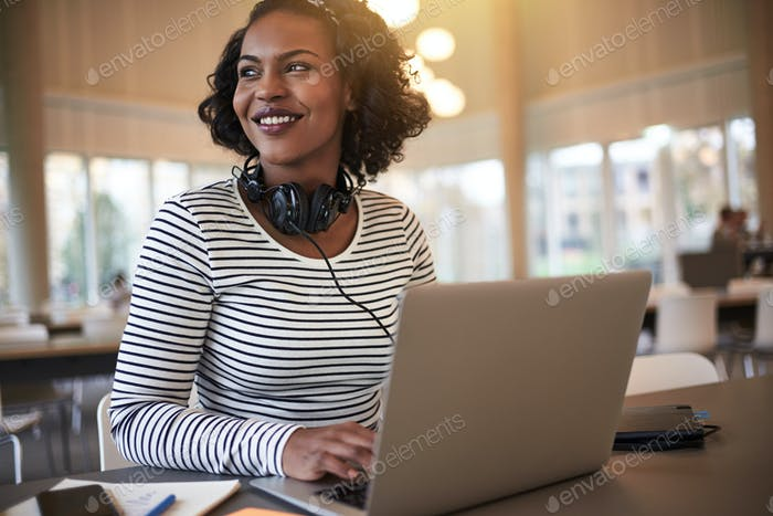 Young African college student smiling while studying at school