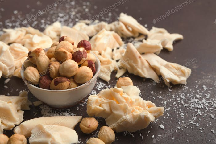 Crushed white chocolate pieces and hazelnuts on gray background
