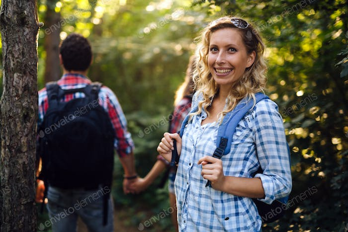 Group of backpacking hikers going for forest trekking