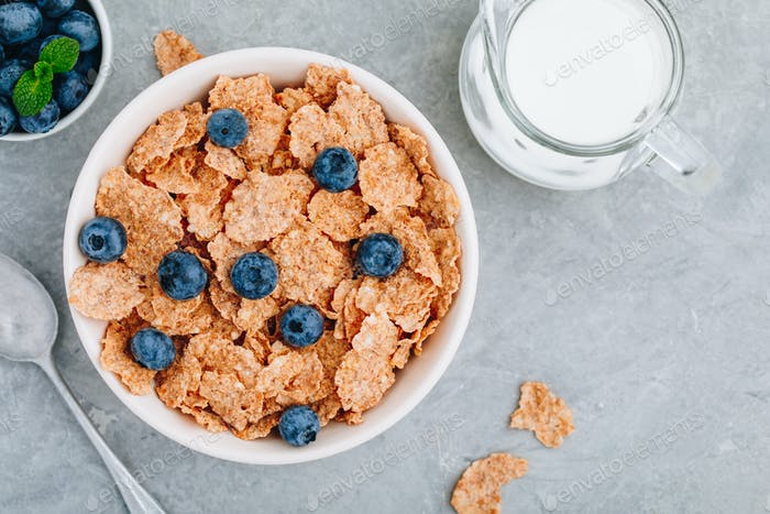 Whole grain breakfast cereal flakes with fresh blueberries and milk. Top view, copy space