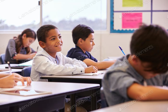 Elementary school kids working at their desks in a classroom
