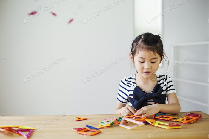 A girl sitting playing with coloured geometric shapes.
