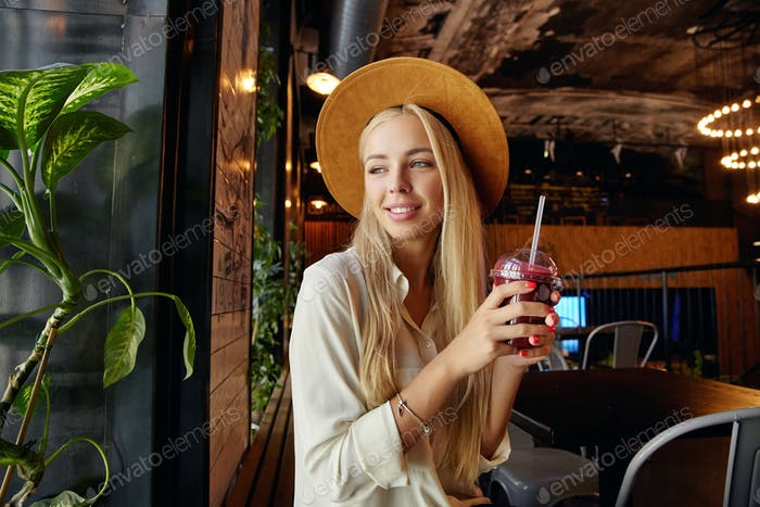 Beautiful long haired blonde woman dressed in stylish clothes sitting over restaurant