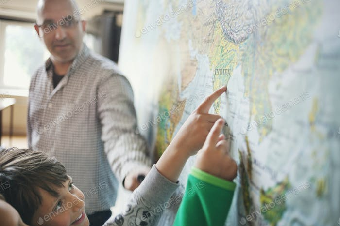Professor looking at students pointing at map