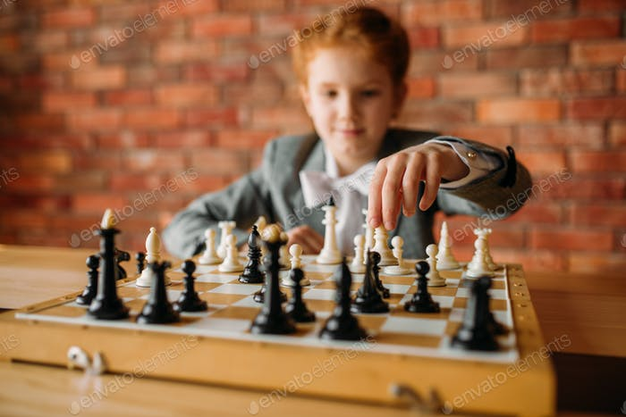Clever schoolgirl, chess player at the table
