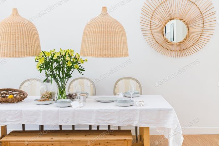 Grey plates, vine glasses and yellow flowers in vase in trendy dining room interior