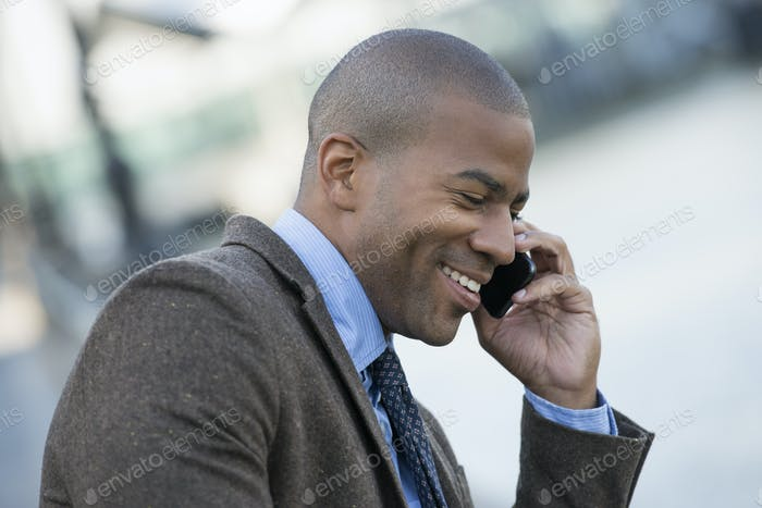 Business man seated on a bench, making a call on his smart phone.