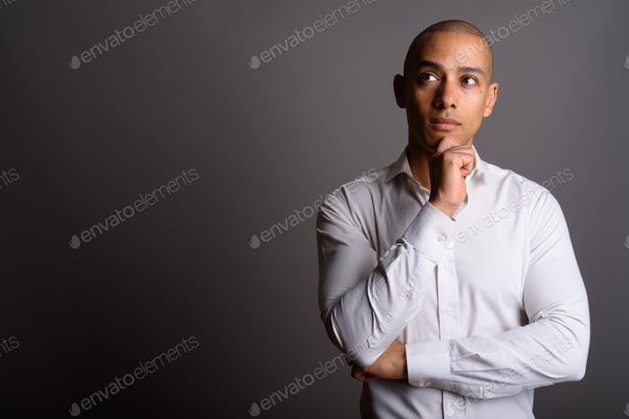Handsome bald businessman thinking and planning with hand on chin