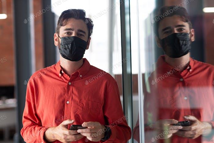 Porträt eines kaukasischen Geschäftsmannes mit Gesichtsmaske, der mit dem Smartphone im Korridor steht