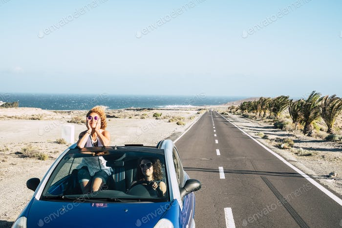 Travel friends with blue convertible car and couple