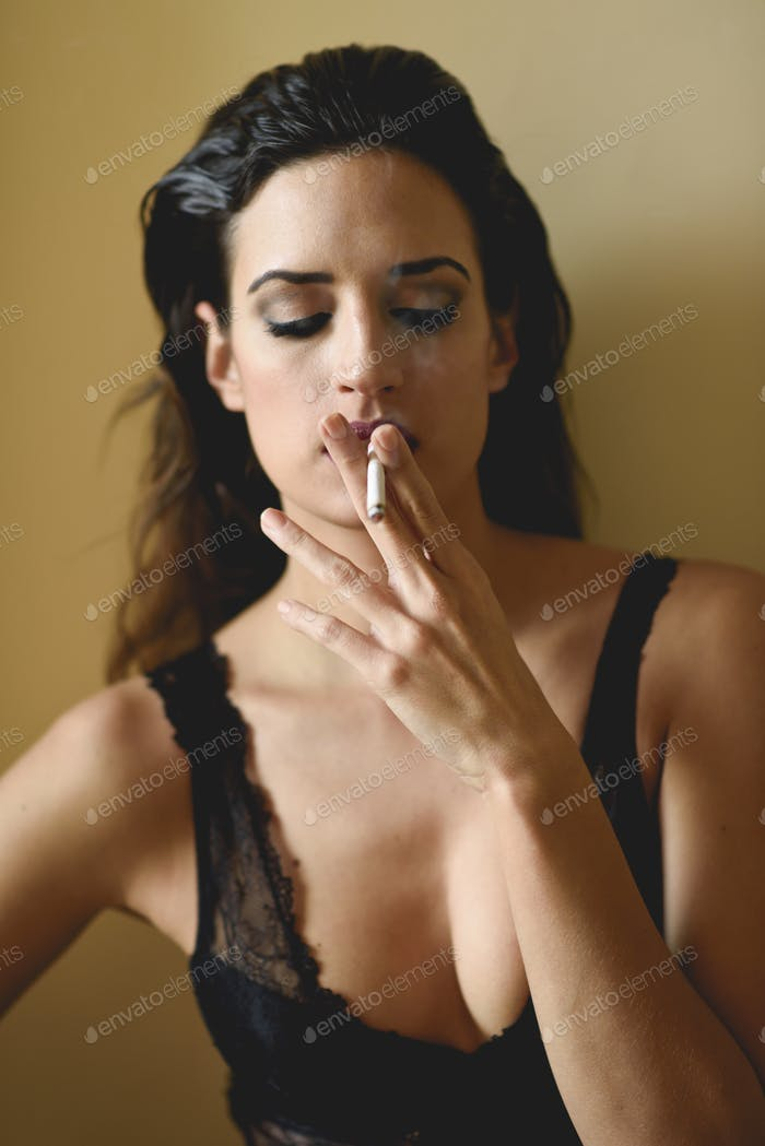 Young woman in black lingerie smoking cigarette