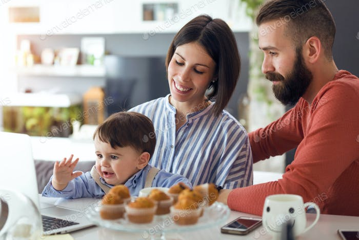 Beautiful young parents with they baby looking cartoons on laptop at home.