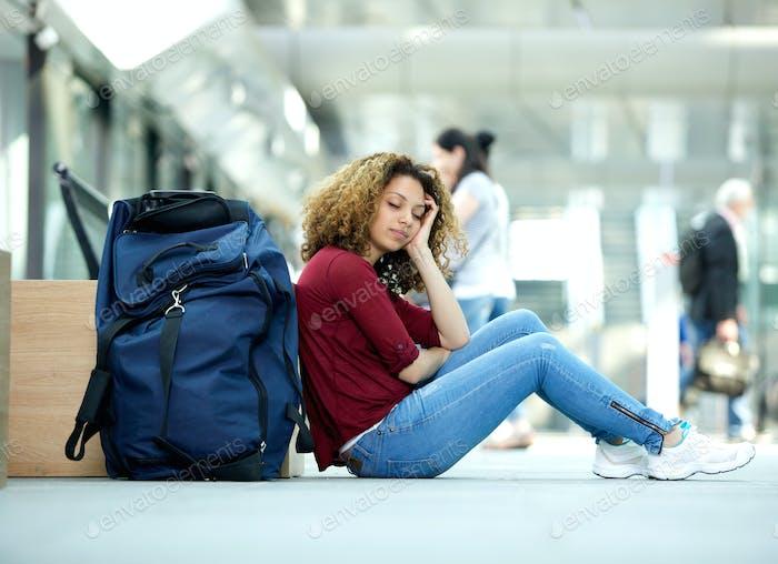 Mujer durmiendo en el aeropuerto con equipaje