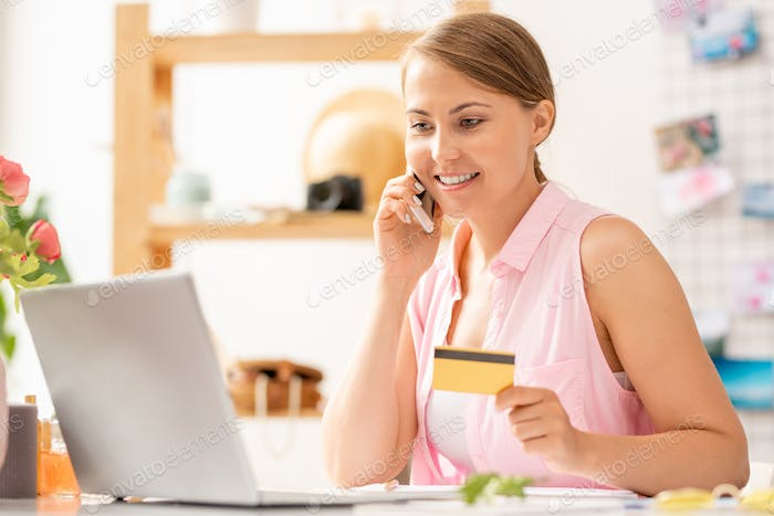 Pretty young woman with smartphone and credit card making order in the net