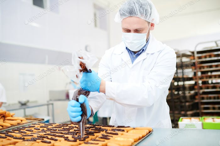 Confectionery factory worker decorating pastry using icing bag