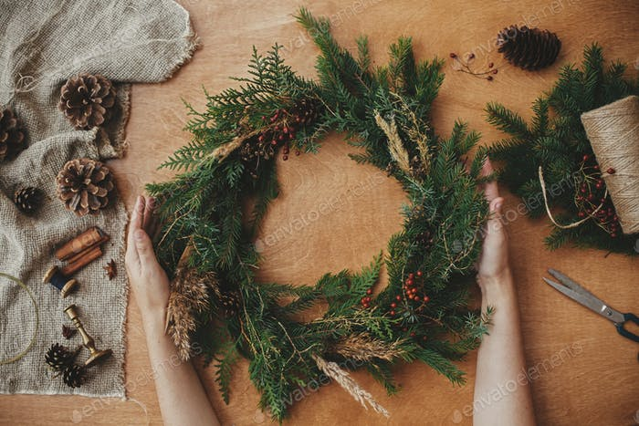 Hands holding christmas wreath with fir branches, berries, pine cones, and thread