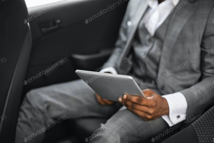Cropped of african businessman going by car, using pad